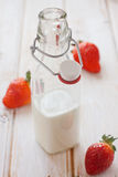 Strawberries and milk bottle Stock Photos