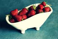 Strawberries in minature bathtubs Stock Photos