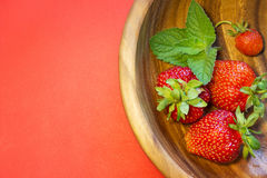 Strawberries and a mint leaf in a wooden plate. Tasty strawberries and a mint leaf in a wooden plate on a red background. Top view cpmposition. Place for text Royalty Free Stock Image