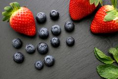 Strawberries, mint leaves and blueberries on black slate background. Three ripe strawberries with some mint leaves and group of blueberries on black slate Stock Photography