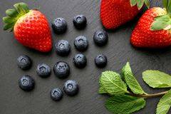 Strawberries, mint leaves and blueberries on black slate background. Three ripe strawberries with some mint leaves and group of blueberries on black slate Royalty Free Stock Photo