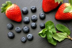 Strawberries, mint leaves and blueberries on black slate background. Three ripe strawberries with some mint leaves and group of blueberries on black slate Royalty Free Stock Image