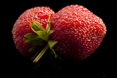Strawberries, mouth, minimalist, fruit, red, macro. Two ripe strawberries with mouth shape. Shoot in studio on black background. Still life Stock Photography