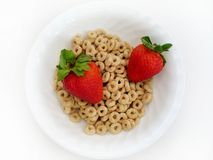 Strawberries and O's. Two juicy strawberries in a bowl of cereal o's. High key, Focus on all subjects royalty free stock photo