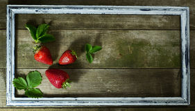 Strawberries in the old frame. On a wooden background stock photography