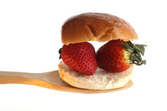 Strawberries ona bun  a wooden spoon Royalty Free Stock Image