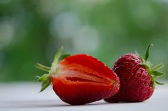 Strawberries, one and one half on wooden table Royalty Free Stock Photos