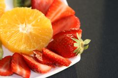 Strawberries and Oranges. Slices of fresh strawberries and fresh oranges on a white plate with black background Stock Photo