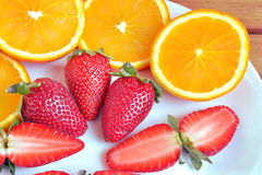 Strawberries and oranges. Cut and ready to eat Stock Photo