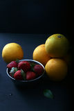 Strawberries and oranges on dark background Stock Photo