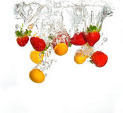 Strawberries and oranges falling Stock Photography