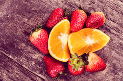 Strawberries and oranges on wood Royalty Free Stock Photography