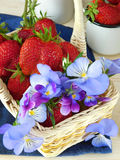 Strawberries and pansies in a wicker basket Stock Photo