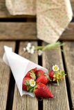 Strawberries in a paper bag. On wooden background stock photography