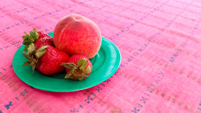 Strawberries and Peach in a Plate Stock Images