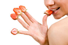 Strawberries picked on fingertips. Sweet caucasian girl eating strawberries picked on fingertips Stock Photography