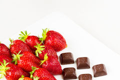 Strawberries and pieces of chocolate in white dish isolated on white background. Close up view. Royalty Free Stock Image