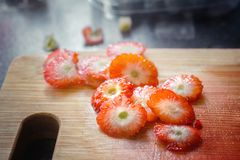 Strawberries pieces cut as leftover after preparing a dessert. Close up Stock Photos