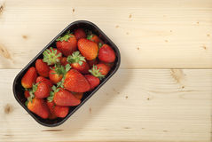 Strawberries on plastic basket. Natural wood Stock Images