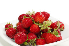 Strawberries on a plate. A white plate full of red, ripe strawberries, shot on white stock images