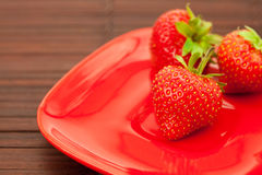 Strawberries and  plate on a bamboo mat Stock Images