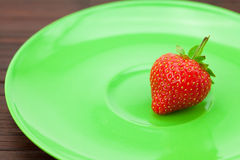 Strawberries and  plate on a bamboo mat Stock Photography