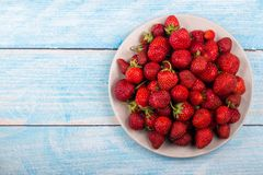 Strawberries on a plate on a blue wooden background royalty free stock photo
