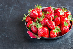 Strawberries in a plate on concrete background. Ripe red strawberries in the iron plate on a dark concrete background Royalty Free Stock Images