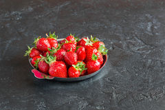 Strawberries in a plate on a dark background. Ripe red strawberries in the iron plate on a dark concrete background Royalty Free Stock Image