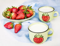 Strawberries on a plate and milk in ceramic cups Stock Image
