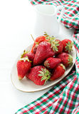 Strawberries on plate and milk over light background Stock Photo
