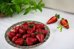 Strawberries on a plate, with mint, spring royalty free stock photography