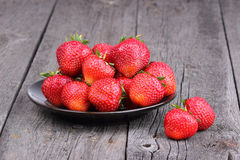 Strawberries on the plate on old wood Stock Photography