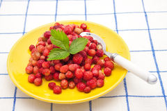 Strawberries on a plate with spoon. Strawberries on a yellow  plate with green leaf and spoon Stock Photos