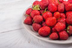 Strawberries on a plate on a white wooden background stock images