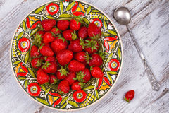 Strawberries in plate on wooden background. Stock Photography