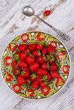 Strawberries in plate on wooden background. Royalty Free Stock Image