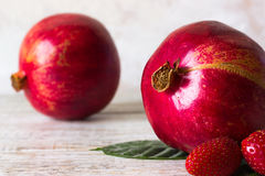 Strawberries and pomegranates closeup. Fruits and berries on a light background Stock Image