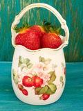 Strawberries in a porcelain vase. Ripe red strawberries in a porcelain vase on a blue background Royalty Free Stock Image