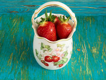 Strawberries in a porcelain vase. Ripe red strawberries in a porcelain vase on a blue background Stock Photography