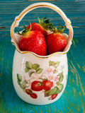 Strawberries in a porcelain vase. Ripe red strawberries in a porcelain vase on a blue background Royalty Free Stock Photo