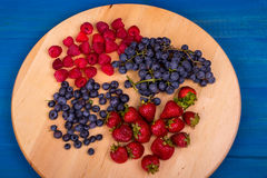 Strawberries, raspberries,  blueberries and grapes on wooden plate Stock Images