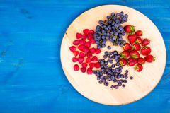 Strawberries, raspberries,  blueberries and grapes on wooden plate Stock Photo