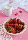 Strawberries and raspberries in a plate. On pink background royalty free stock photography