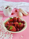 Strawberries and raspberries in a plate. On pink background royalty free stock photo