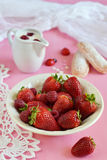 Strawberries and raspberries in a plate. On pink background stock photography