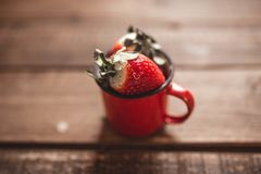 Strawberries in a red enamel mug on a wooden table royalty free stock photos