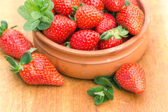 Strawberries in rustic bowl Stock Images