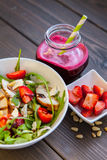 Strawberries salad with pine nuts, arugula and chicken. Royalty Free Stock Image