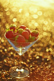 Strawberries on a sandy beach in a glass bowl. Everything is bathed in warm light, bright golden sunbeams. A gentle, artistic, blurry image. Sunny summer mood stock photography